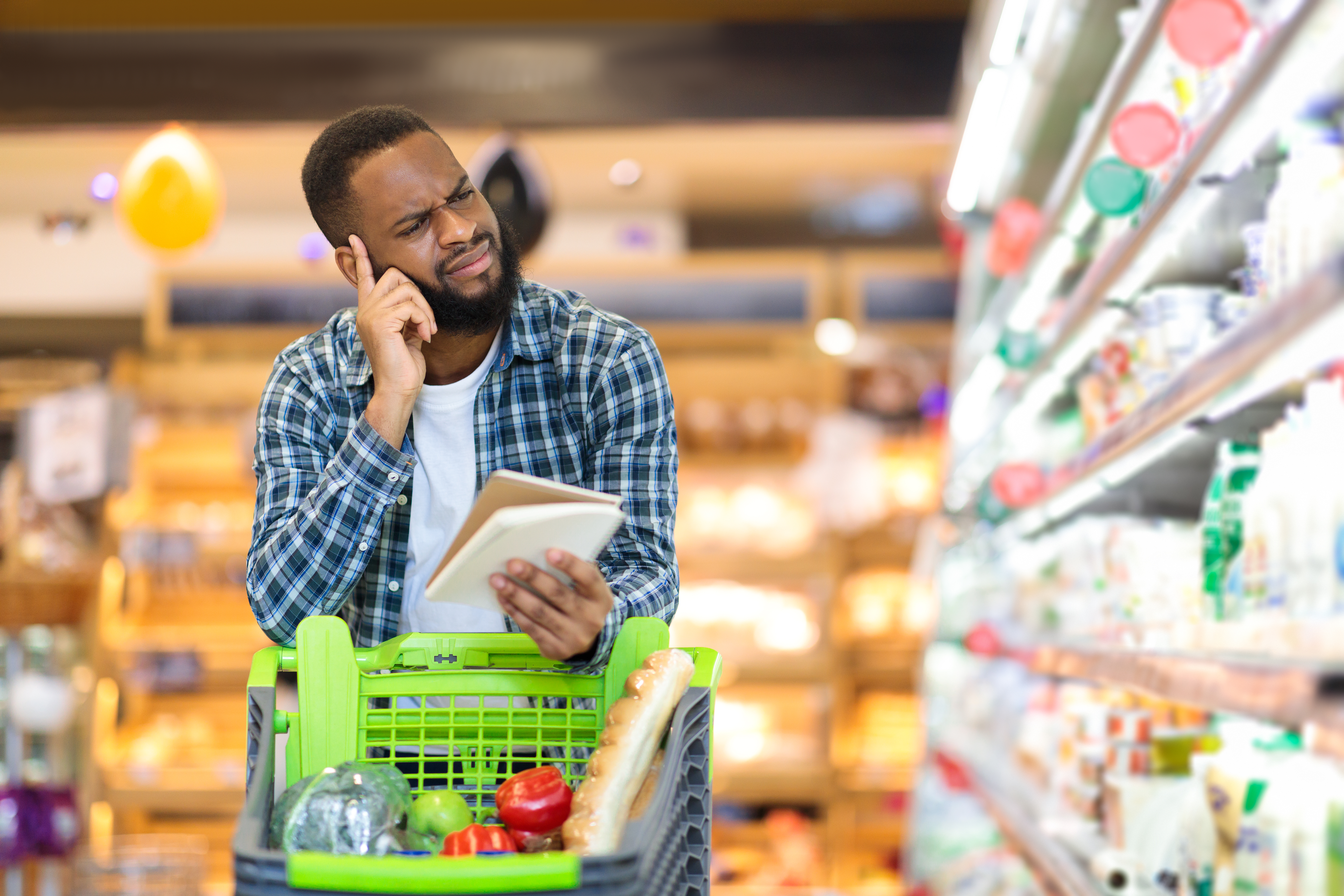 african-man-buying-food-with-groceries-checklist-s-26FVNXV